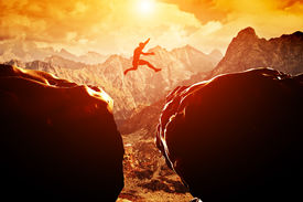 pic of risk  - Man jumping over precipice between two rocky mountains at sunset - JPG