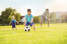 pic of football pitch  - Young father with his little sons playing football on football pitch - JPG