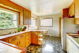 stock photo of linoleum  - Kitchen room with honey rustic storage cabinets shiny linoleum floor and small dining area - JPG