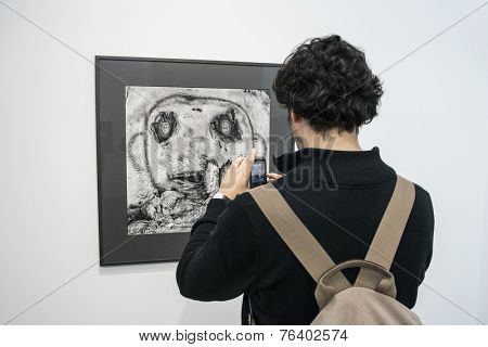 People taking a photo of a photo of Roger Ballen at Paris Photo art fair 2014, Paris, France
