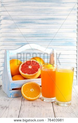 Orange and carrot juice in glasses and fresh fruits in wooden box on wooden table on wooden wall background