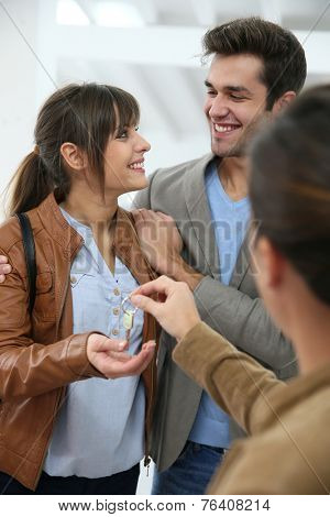 Happy young couple getting key of their new place
