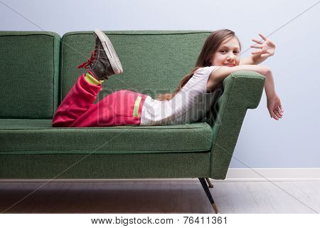 Little Girl Waving At The Camera Lying On A Green Sofa