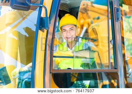 Asian driver sitting in cockpit of construction machinery of building site or mining or rental company