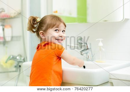 Cute little girl washing in bathroom