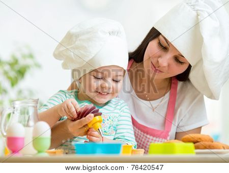 Mother and kid girl making cookies