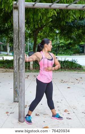 Sporty woman stretching upper arm by wooden post in exercise park