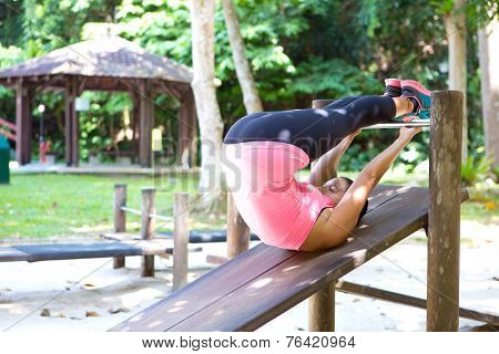 Beautiful woman doing reverse crunches for abdominal muscle in outdoor exercise park