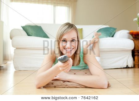 Young Woman Watching Tv Lying On The Floor