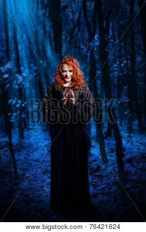 Young witch in the night forest
