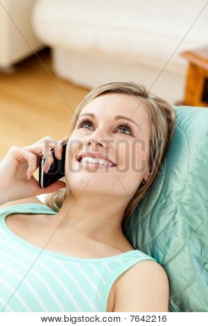 Smiling Young Woman Talking On Phone Lying On A Sofa