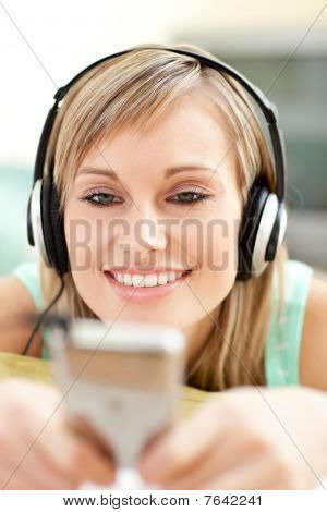 Joyful Young Woman Listening Music Lying On A Sofa