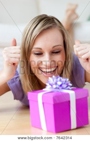 Joyful Woman Looking At A Gift Lying On The Floor