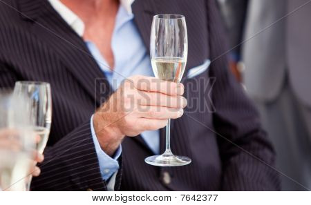 Close-up Of A Senior Businessman Holding A Glass Of Champagne