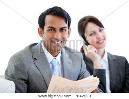 Smiling Businessman Reading A Newspaper In A Waiting Room
