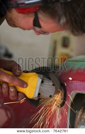 Car Mechanic Using A Grinder In His Garage