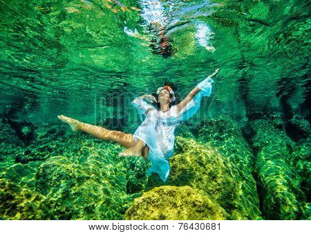 Attractive female wearing fashion costume dancing in transparent turquoise water, diving to the sea bottom, freedom and enjoyment concept