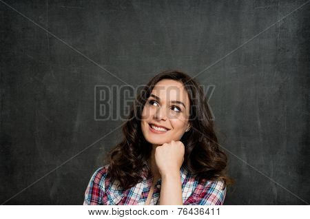 Happy Young Woman Contemplating Over Gray Background