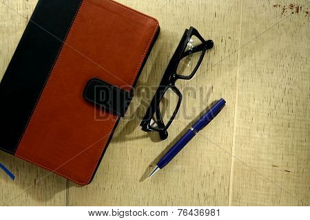 Notebook with leather cover, pen and eyeglasses