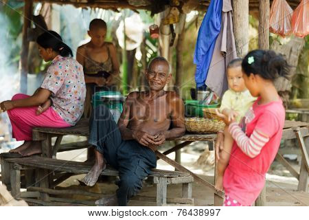 SIEM REAP, CAMBODIA, DECEMBER 04, 2012: A happy farmer family is relaxing under a wooden hut in the countryside of Siem Reap, Cambodia