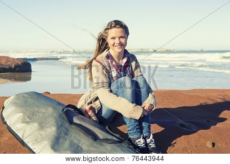 Teenage girl at the beach with her surfboard and waiting for the waves