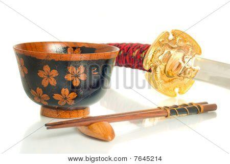 Katana, Chopsticks And Bowl Over White