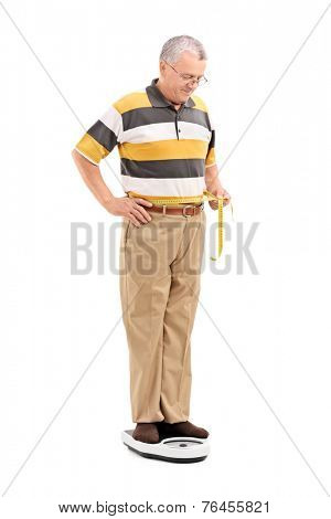 Mature man measuring his waist and standing on a weight scale isolated on white background