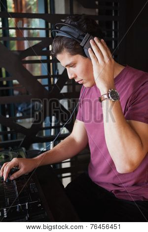Cool dj working on a sound mixing desk at the nightclub
