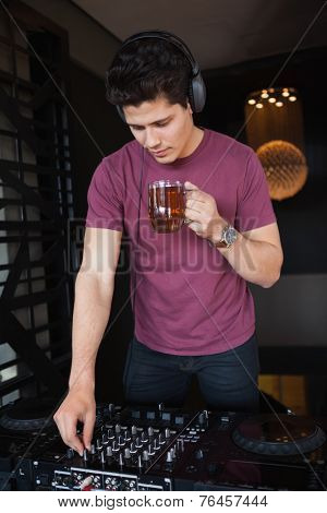 Handsome focused dj moderating turning up volume at the nightclub