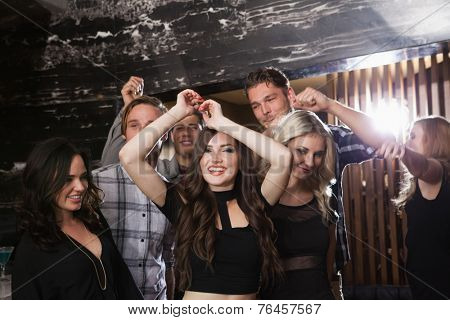 Stylish friends dancing and smiling at the nightclub