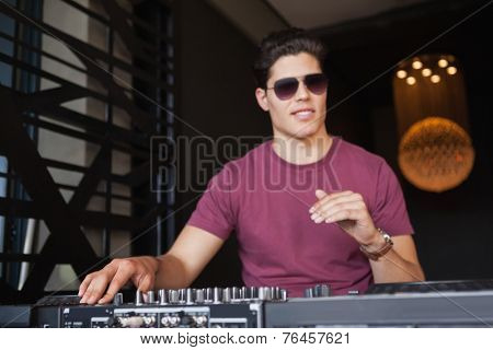 Cool dj in sunglasses working on a sound mixing desk at the nightclub