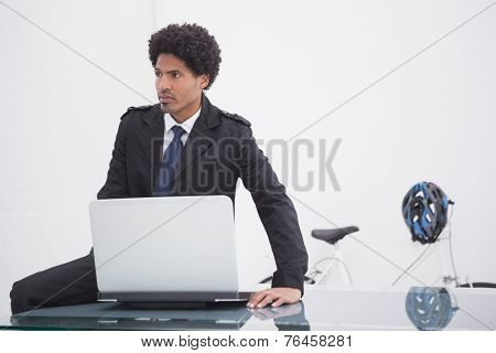 Thoughtful businessman in trench coat using laptop in his office