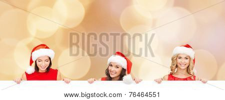 christmas, x-mas, people, advertisement and sale concept - happy women in santa helper hat with blank white board over beige lights background
