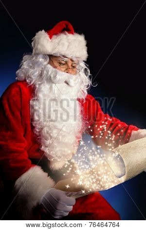 Santa Claus in costume holding wish list. Dark pattern as background