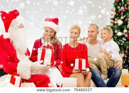 family, holidays, generation, christmas and people concept - smiling family with santa claus and gift boxes at home