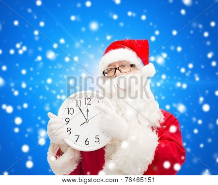 christmas, holidays and people concept - man in costume of santa claus with clock showing twelve over blue snowy background