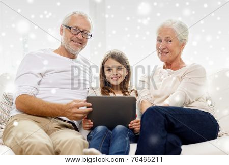 family, generation, technology and people concept - smiling grandfather, granddaughter and grandmother with tablet pc computer sitting on couch at home