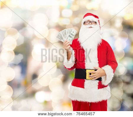 christmas, holidays, winning, currency and people concept - man in costume of santa claus with dollar money over lights background