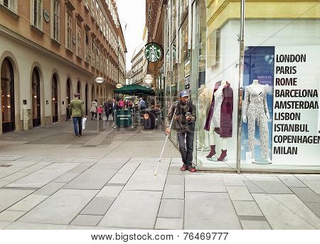Beggar Standing Next To A Fashion Store
