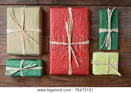 High angle shot of a group of presents wrapped with colorful tissue paper. The gifts are tied with raffia and are laying on a rustic wood table. Horizontal format.