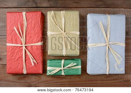 High angle shot of a four presents wrapped with colorful tissue paper. The gifts are tied with raffia and are laying on a rustic wood table. Horizontal format.
