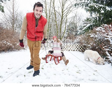 Smiling couple outdoors on toboggan with christmas gifts and dog