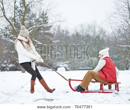Laughing woman pulling man on sled through snow in winter