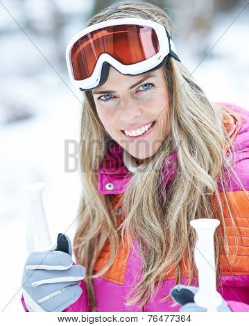 Happy woman in winter with ski googles on a ski trip holding poles
