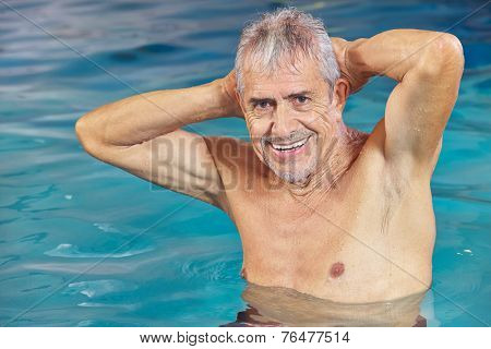 Happy senior man doing aqua fitness in swimming pool in summer