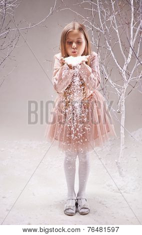 Cute little girl in smart dress blowing snowflakes from her palms in winter forest