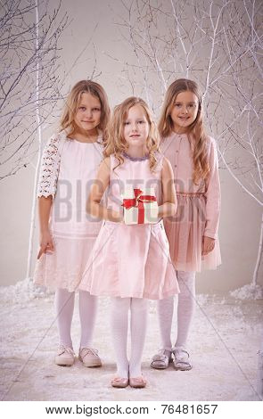 Cute adolescent girl holding giftbox with her two friends near by