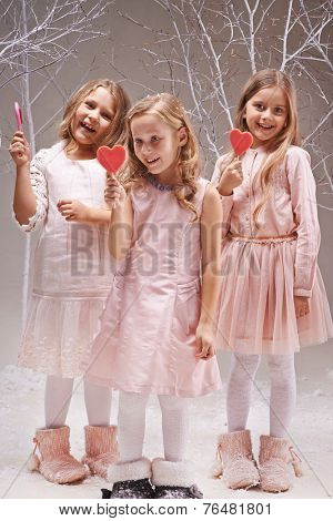 Group of ecstatic girls with candy hearts having fun in fairy garden