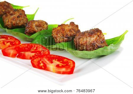 grilled french meat balls with tomatoes on white