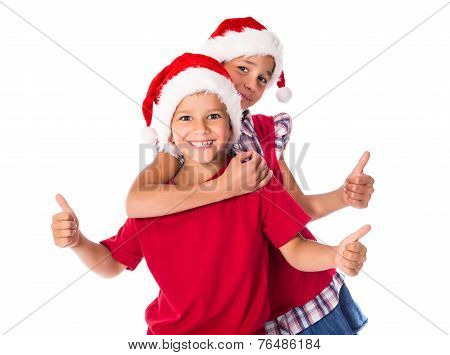 Two kids in Christmas hats together